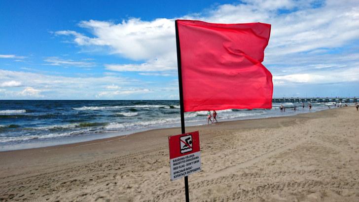 Красный флаг на пляже в Паланге, Литва, 2016